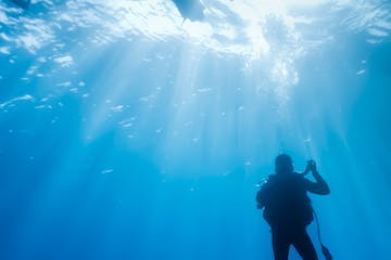 Scuba diver emerging to the surface in the deep blue water.