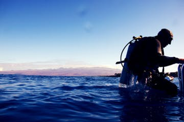 Diver sitting on the edge of boat at dusk