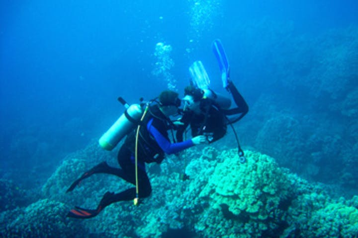Two divers helping each other underwater