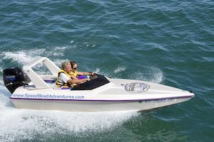 A couple drives in a private speed boat in a speed boat riding along the ocean in San Diego