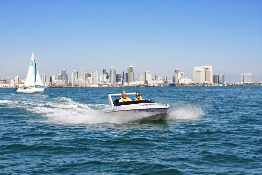 A driver and passenger in a speed boat in a speed boat riding along the ocean in San Diego