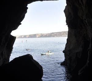 A person paddles on their canoe in the ocean and looks through into the Sunny Jim Cave in San Diego