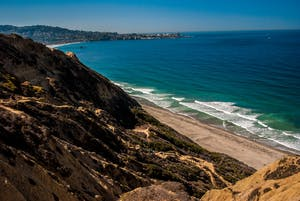 A view of the Blacks Beach in San Diego on a sunny day from the top of the hill