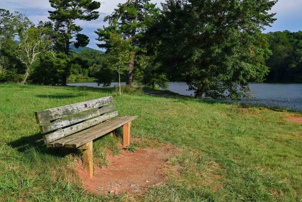a wooden park bench sitting in front of a body of water