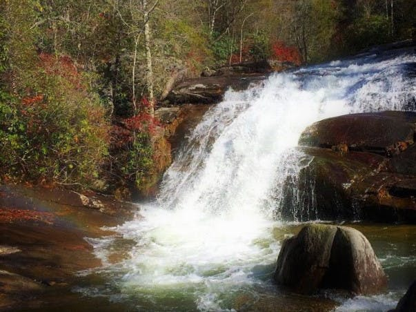 a large waterfall over a body of water with Swallow Falls State Park in the background