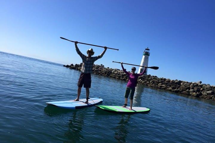 Paddle boarders raising paddles