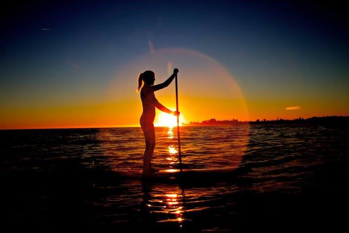 sunset ring around paddle boarder