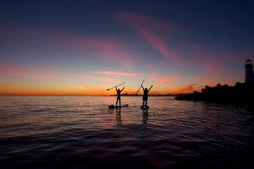 2 paddle boarders raising their hands in the sunset