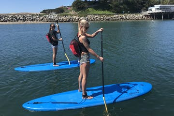two girls paddleboarding