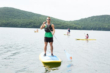 a person paddleboarding on a reservoir with kayaks in the background