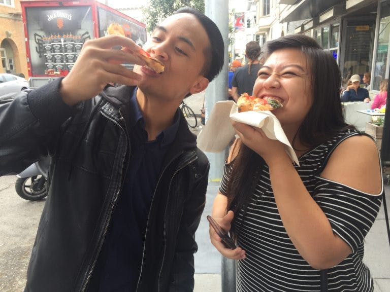 Food tour participants eating street food in New York City