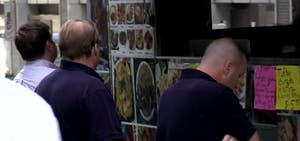 Locals ordering from a food cart in downtown NYC