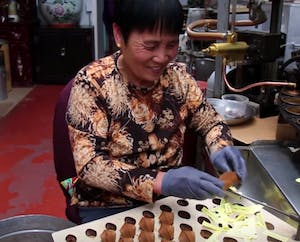 A woman making fortune cookies