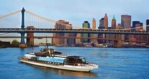 A river cruise boat on the Hudson with NYC in the background
