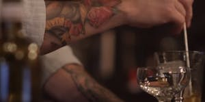 tattooed arms mixing a cocktail in a glass