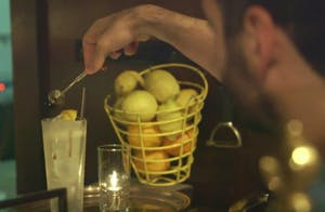a person mixing a cocktail next to a bucket of lemons