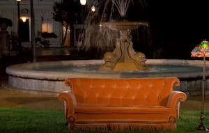 a large orange sofa in front of a fountain