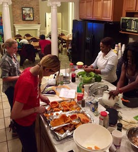 a group of women preparing food in a kitchen