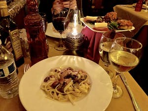 a table with a plate of food, a glass of wine and an oil lamp