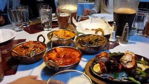 a group of people sitting at a table with four different bowls of foods