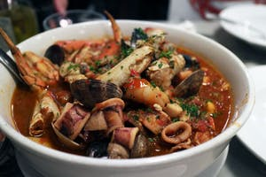 a white bowl filled with a seafood stew