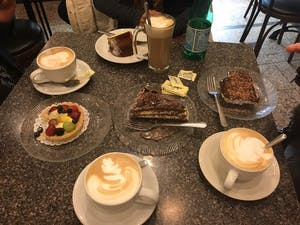 plates of different dessert foods and two cappuccinos