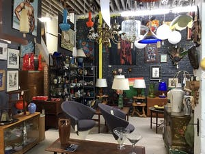 a room with many items and lights on the shelves and hanging