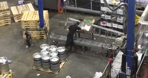 a warehouse with a conveyer belt and several kegs of beer