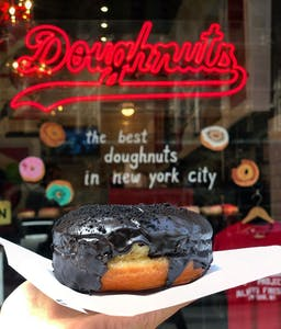 a donut covered in chocolate in front of a donut shop window