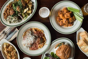 an overview of a variety of dishes including spaghetti and meatballs, buffalo chicken wings, a sandwich, and side dishes