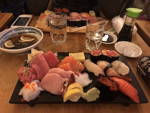 a tray of raw fish and prepared sushi on a table