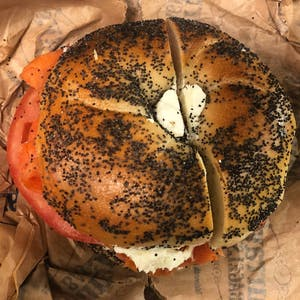 an everything bagel filled with cream cheese and sliced tomato on a paper bag