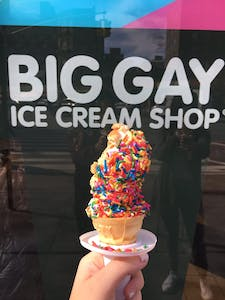 an ice cream cone filled with ice cream and sprinkles in front of an ice cream shop