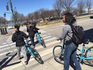 people crossing the street walking bikes
