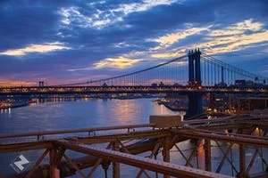 the Brooklyn Bridge with a sunset behind it