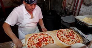 a man preparing two pizzas on a wooden cutting board