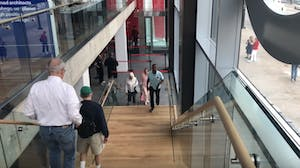 the top view of a set of stairs with people walking in each direction