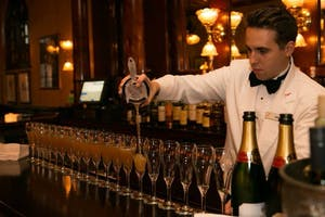 a bar tender pouring cocktails into twenty glasses lined along a bar