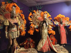 three stuffed statues wearing bright large headdresses