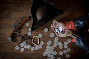 a pirate hat with coins, keys and a gun on a table
