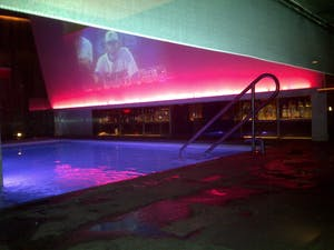 an indoor pool with lights, a bar and a large overhead digital screen