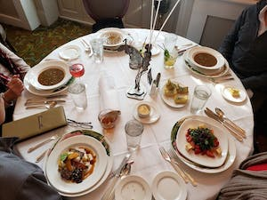 a table set with cloth linens and place settings of soup and fancy meals