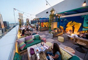 an outdoor rooftop bar with colorful couches and tables