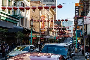 cars driving on a busy city street with Chinese lanterns hanging from the buildings above