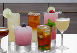 several colorful alcoholic beverages on a bar