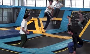 a group of people jumping on indoor trampolines