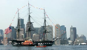 a large ship in the water with USS Constitution in the background