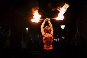 a man standing with a fire stick