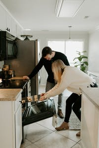a couple that is standing in the kitchen getting something out of the oven
