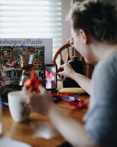 a guy on facetime with a friend while doing a puzzle